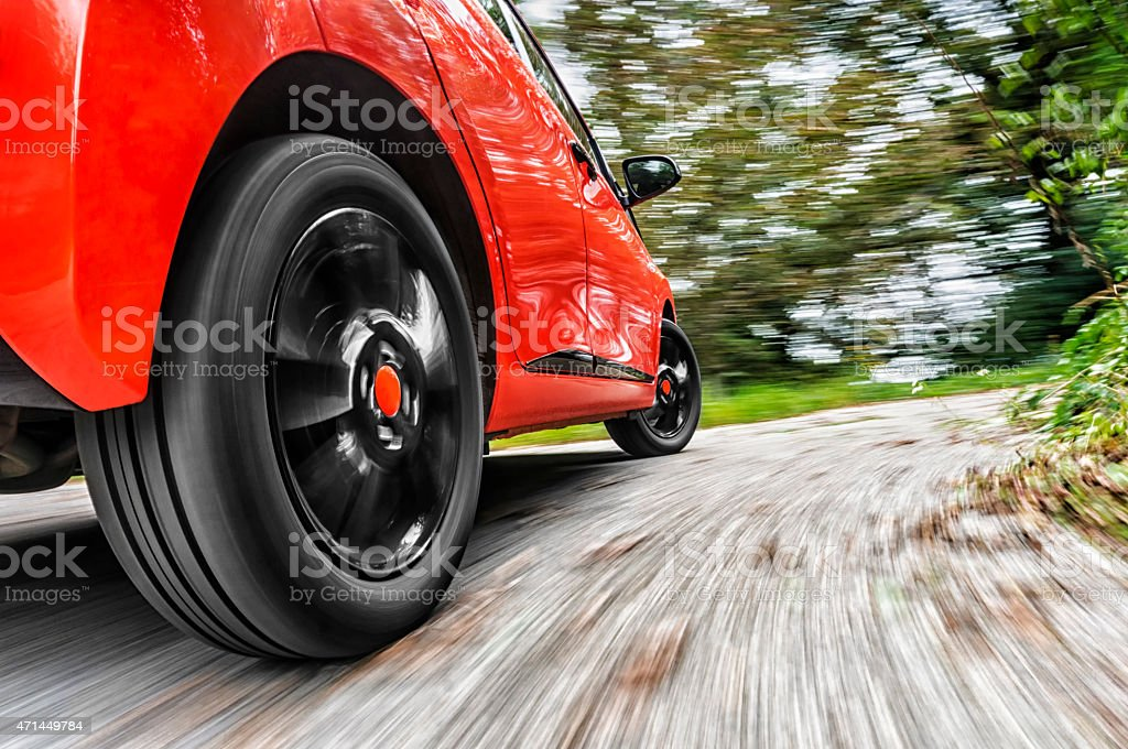 Focus on rear wheel of red car driving - blurry background stock photo
