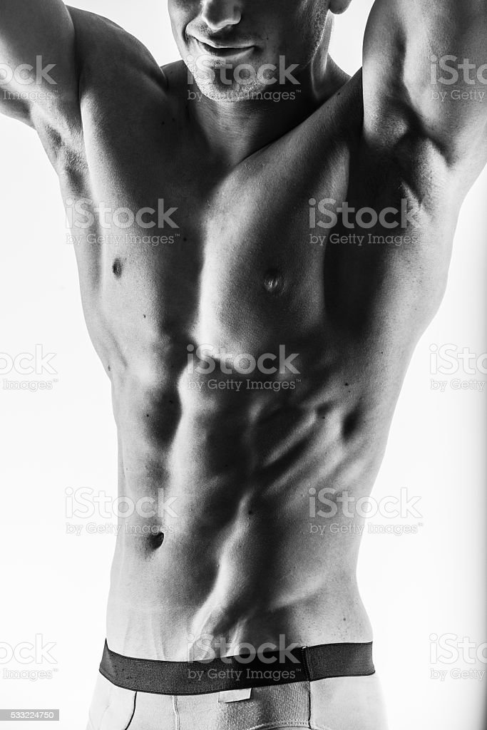 Focus on stomach. Dark contrast shot young muscular fitness man stock photo