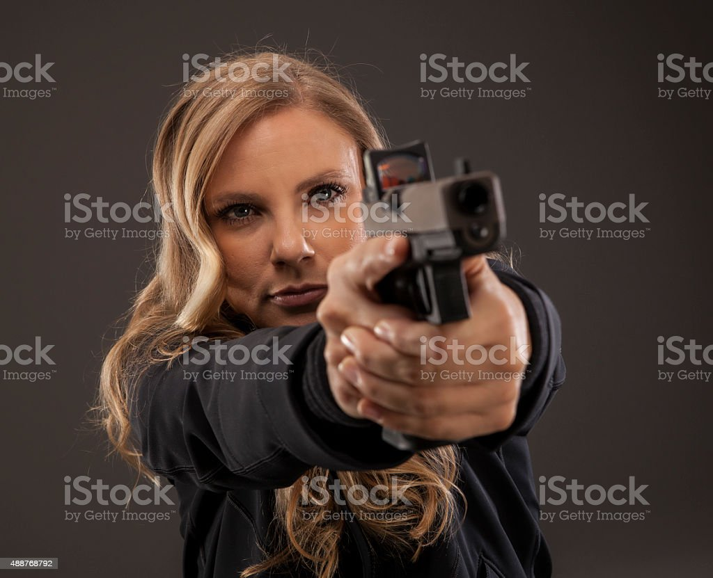 Focus on woman shooter aiming gun. stock photo
