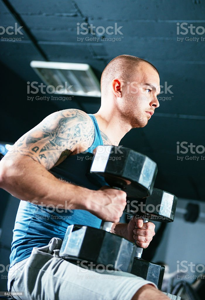 Focused athlete with weights in gym stock photo