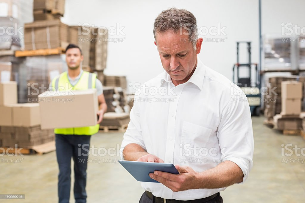Focused boss using digital tablet stock photo