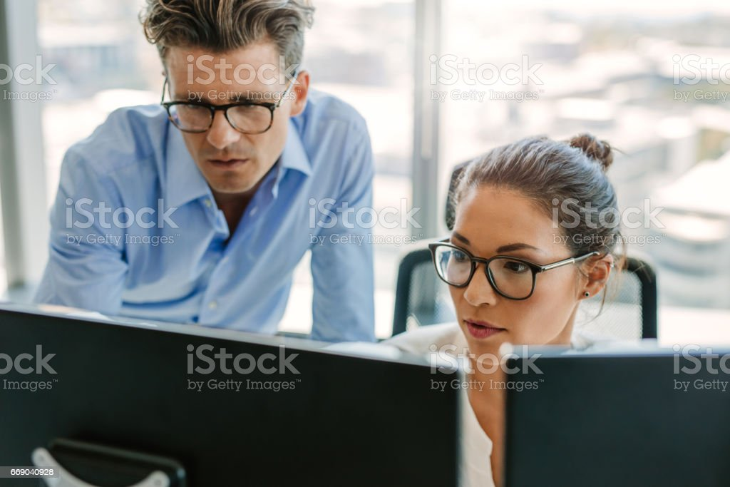 Focused business team using a computer in office stock photo