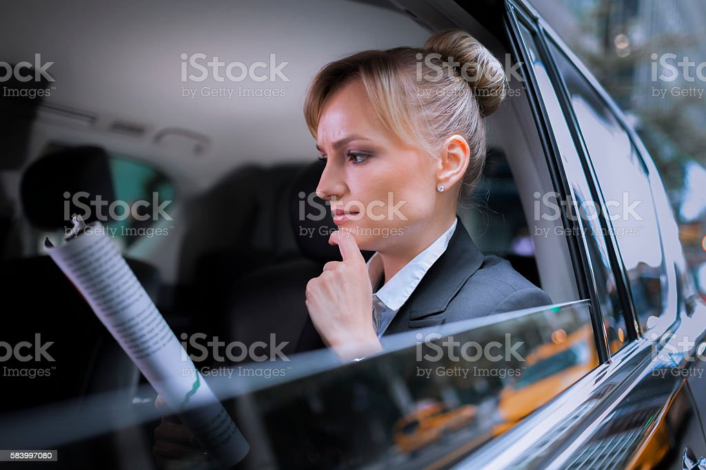 Focused business woman reading report in car stock photo