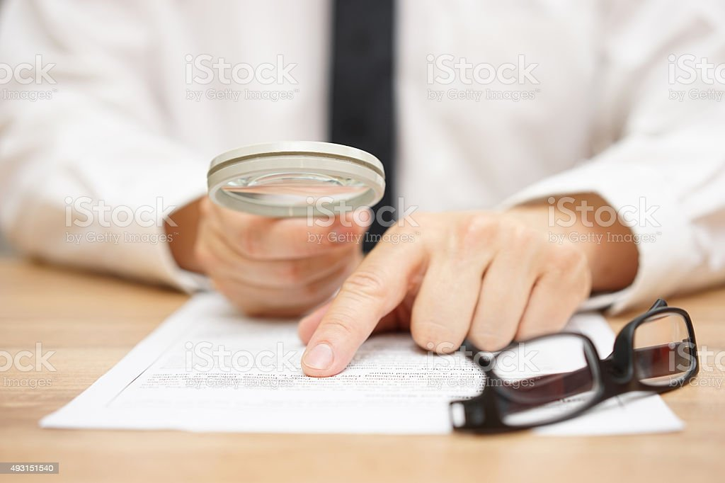 Focused businessman is reading through  magnifying glass document stock photo