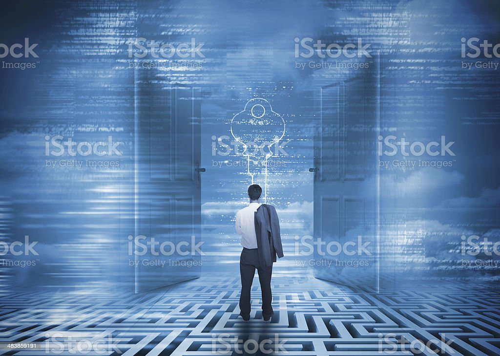 Focused businessman standing on a maze in front of doors stock photo
