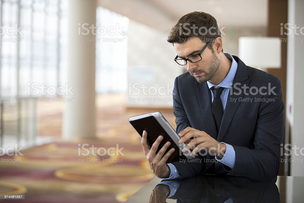 Focused businessman with glasses using tablet at the hotel lobby stock photo