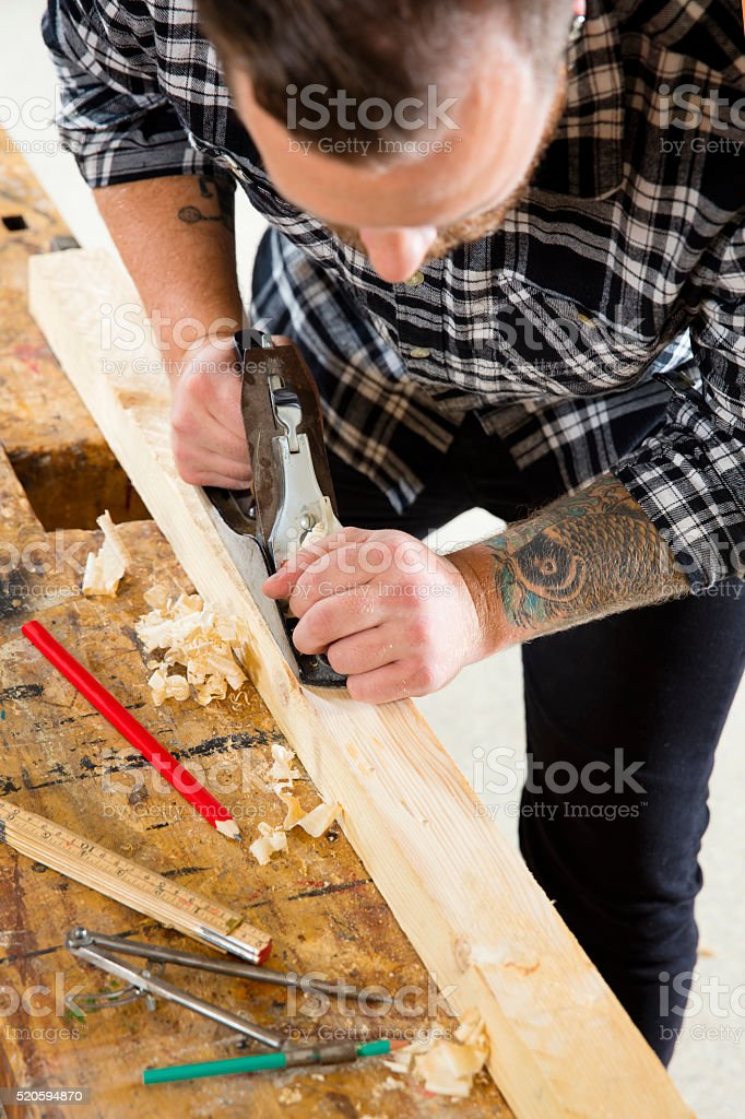 Focused craftsman working with plane on wood plank in workshop stock photo