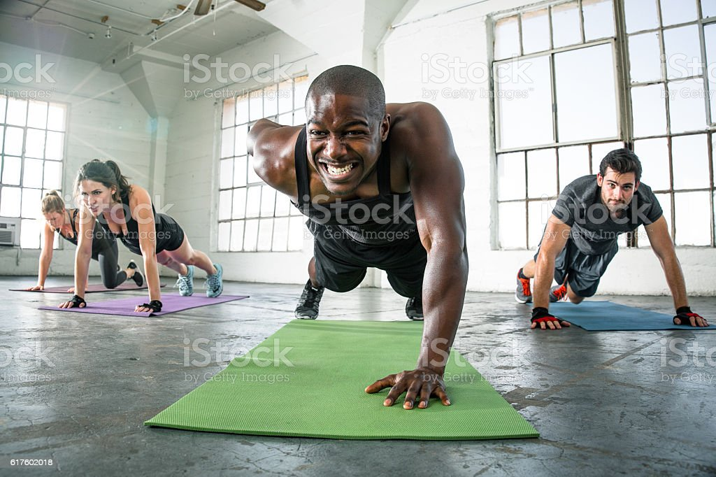 Focused determined powerful strong fitness workout push ups gritting teeth stock photo