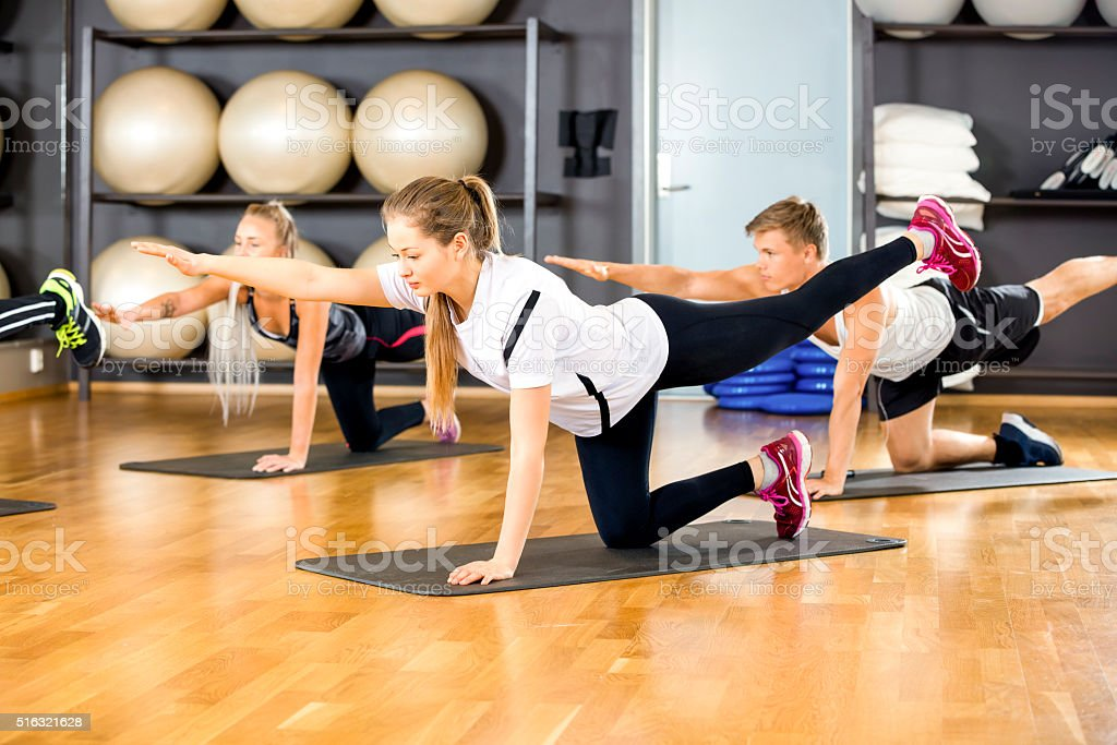 Focused group exercising core strength and balance at fitness gym stock photo