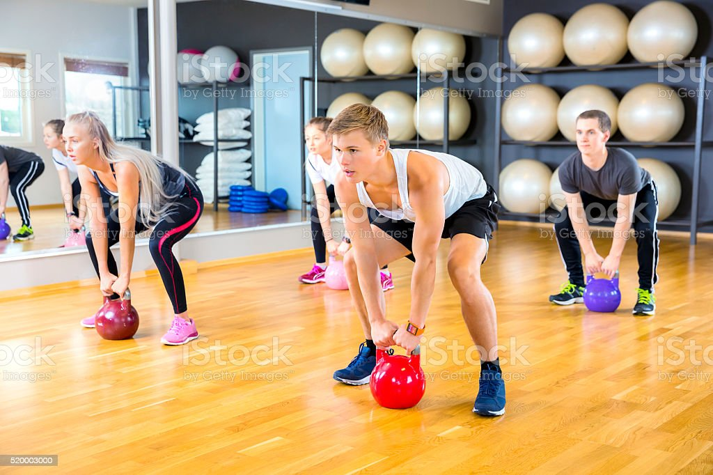 Focused group trains with kettlebells at fitness gym stock photo