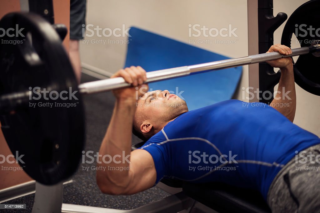 Focused man doing workout on weight bench stock photo