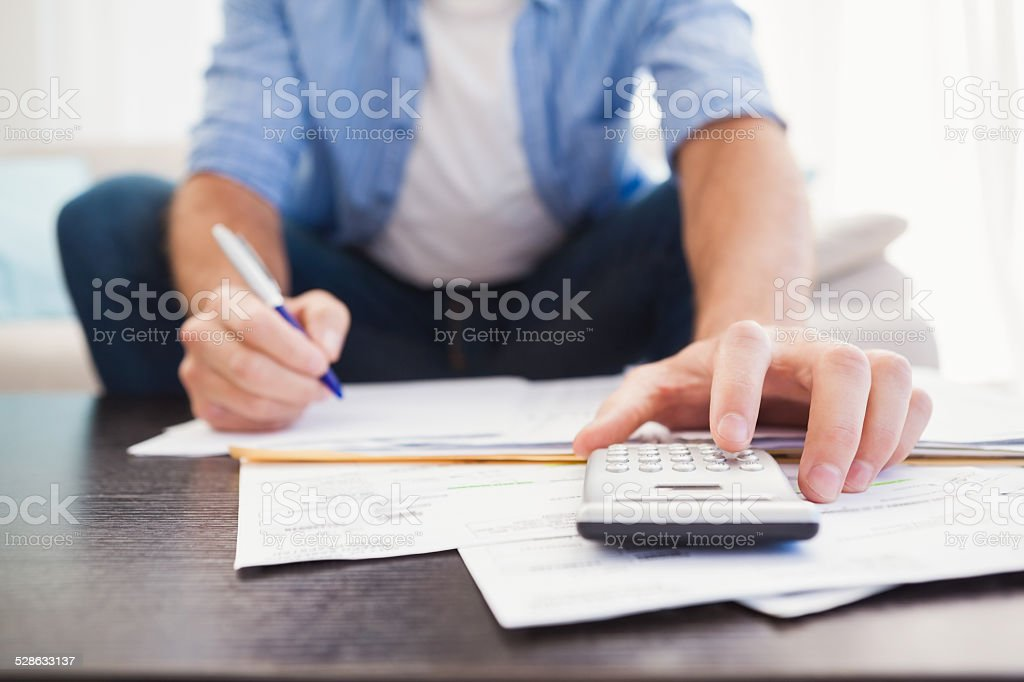 Focused man figuring out his finances stock photo