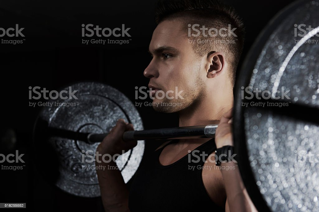 Focused man lifting heavy barbell stock photo