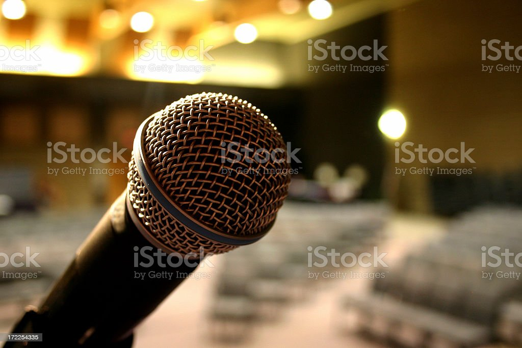 Focused microphone on a blurry, empty auditorium royalty-free stock photo