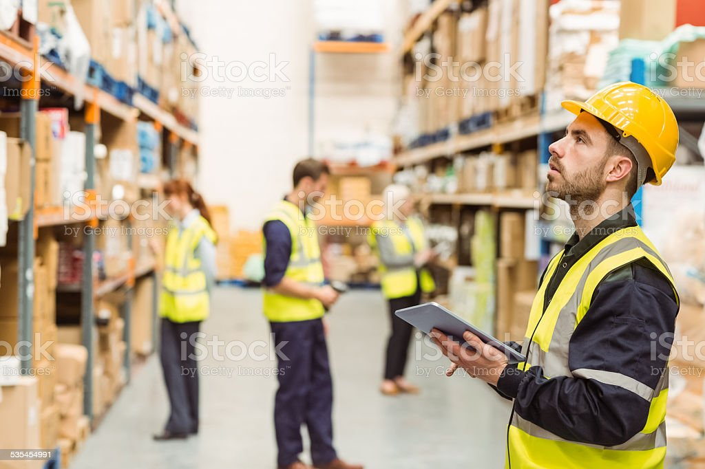 Focused warehouse manager writing on clipboard stock photo