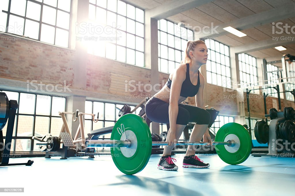 Focused young woman lifting weights in a gym stock photo