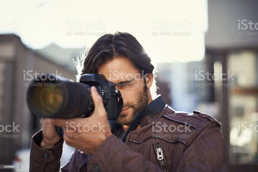 Focusing on his photography skills stock photo