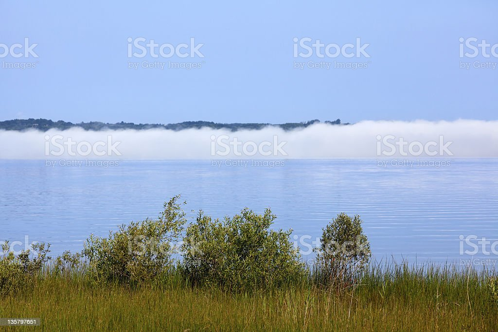 Fog Bank Lifts from Water in Morning Sun stock photo