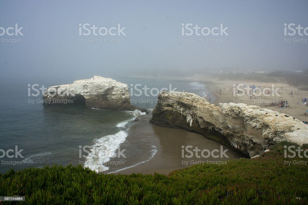 Fog blurs natural bridge and people on beach stock photo