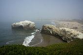 Fog blurs natural bridge and people on beach