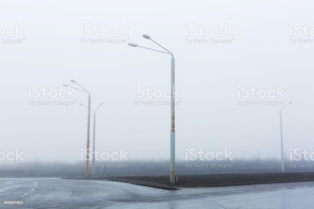 Fog on lonely road. Street lights, foggy misty, lamp post lanterns, deserted road in mist fog, wet asphalt tarmac stock photo