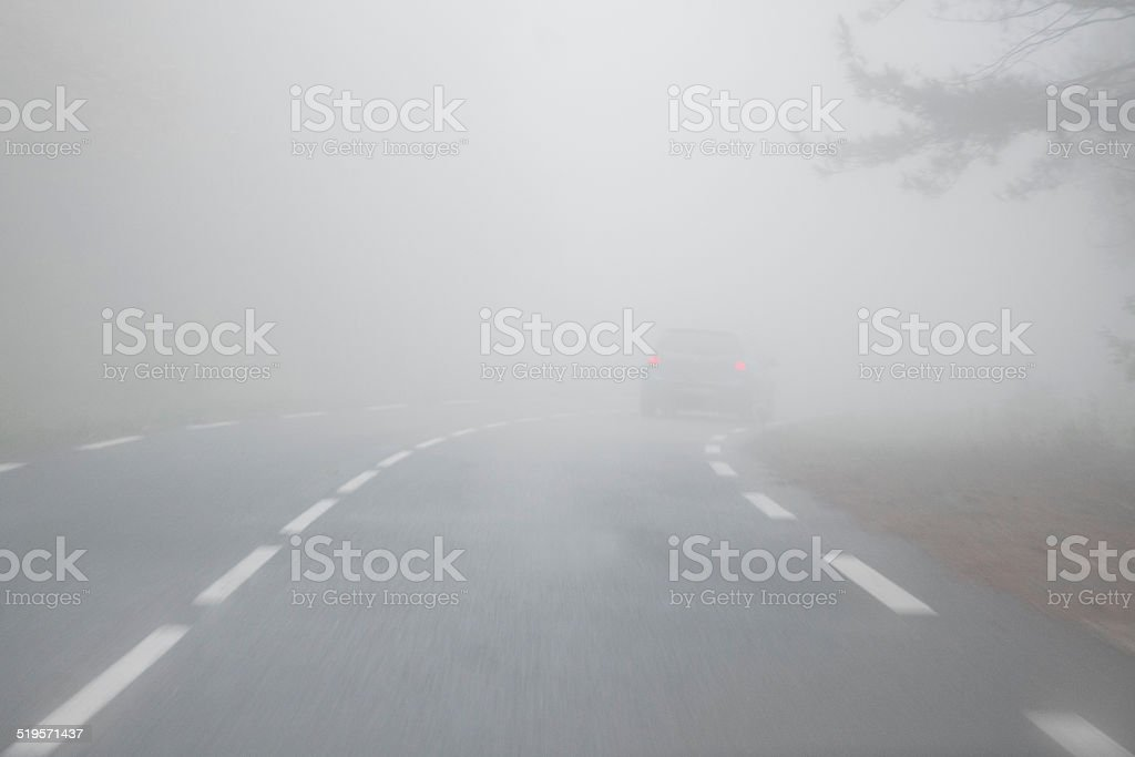 Fog on the road, with a car stock photo