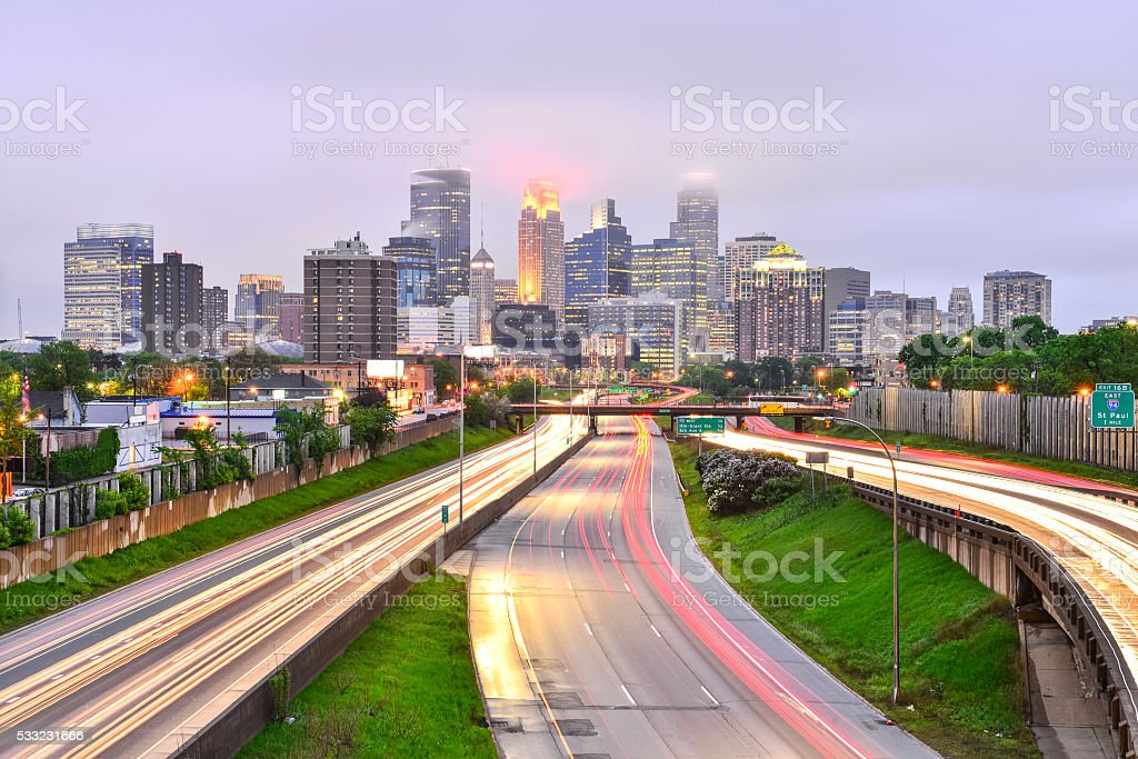 Foggy Minneapolis Skyline at Dusk with Traffic Light Trails stock photo