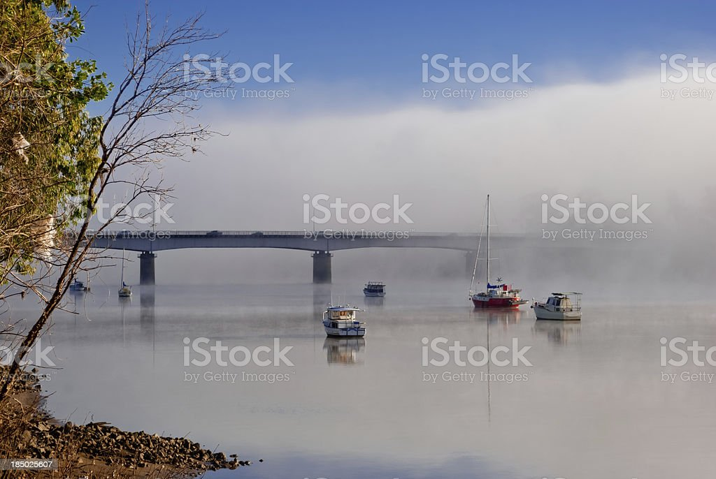 Foggy morning on a river with boats stock photo