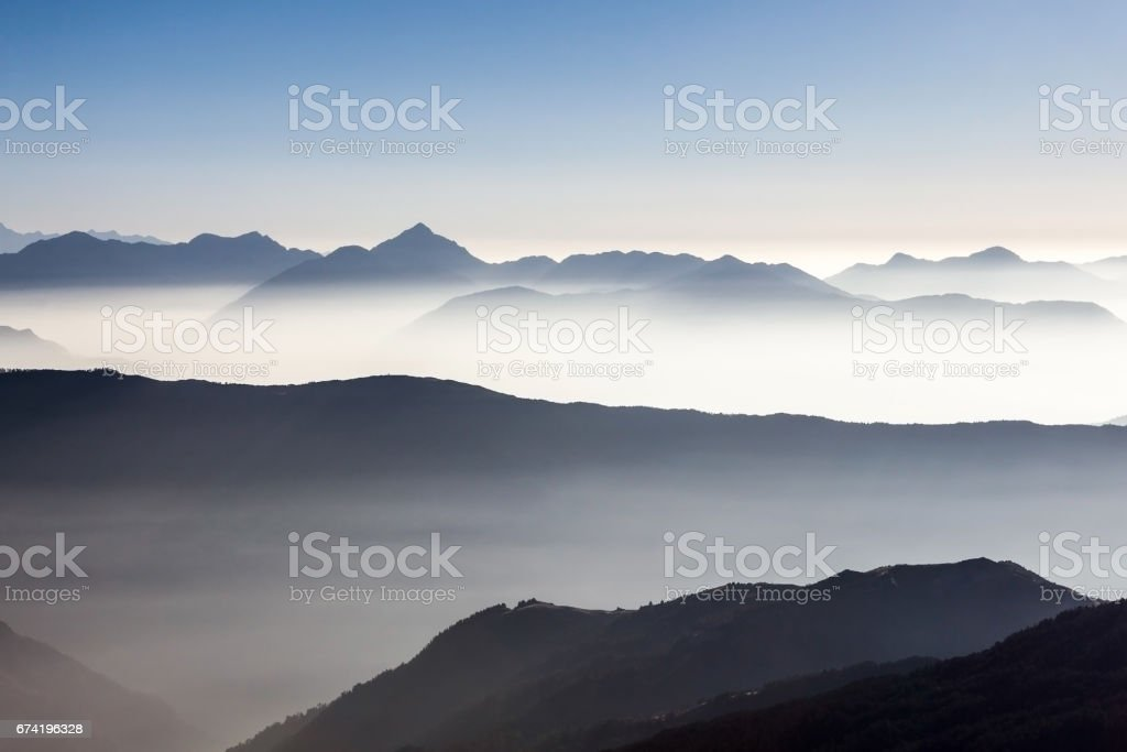 Foggy mountain landscape in Himalayas, Nepal. Beautiful mountain valley filled with early morning mist. Dramatic foggy mountain range rise above white fog Nepal, Himalayas. stock photo