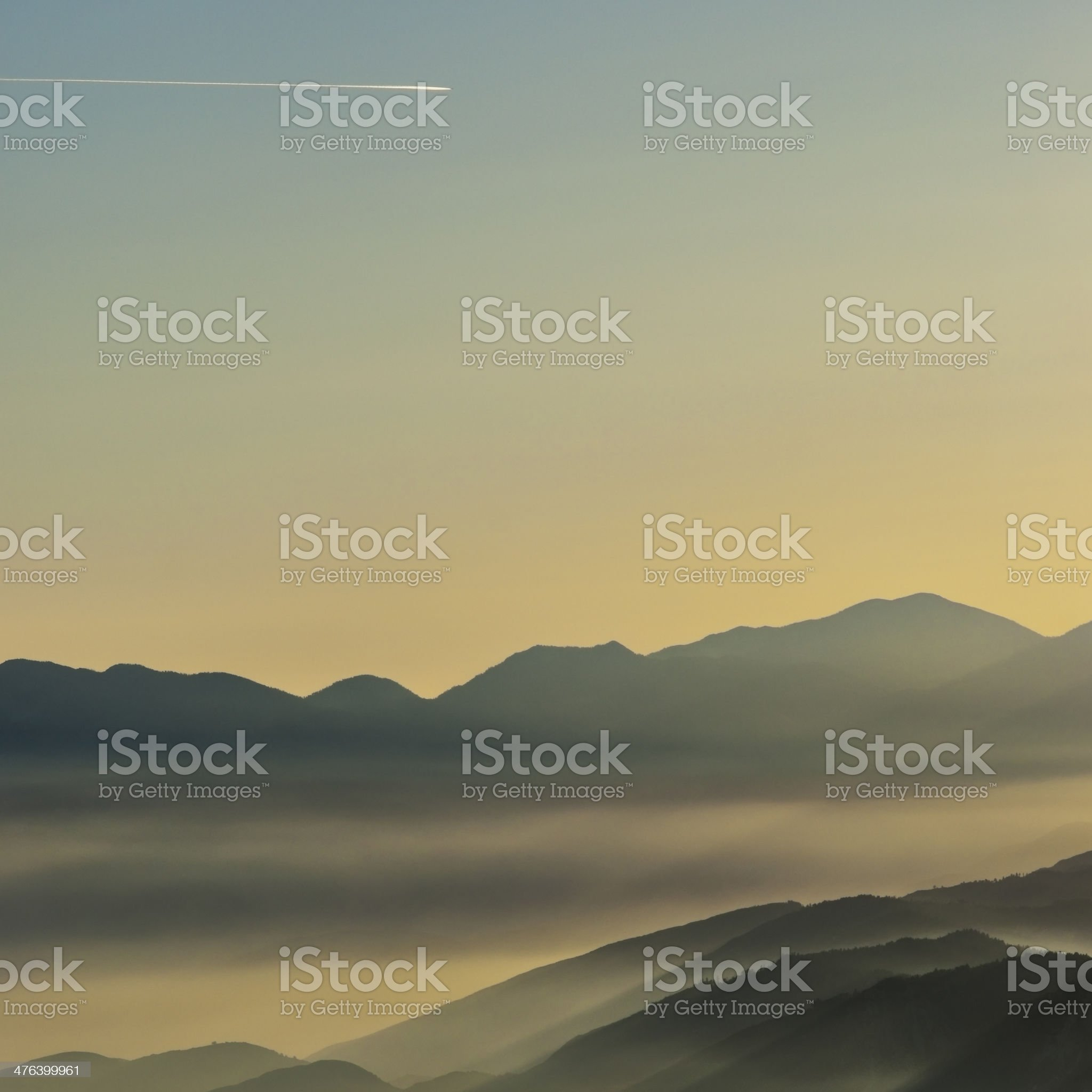 Foggy Mountains and Contrail royalty-free stock photo