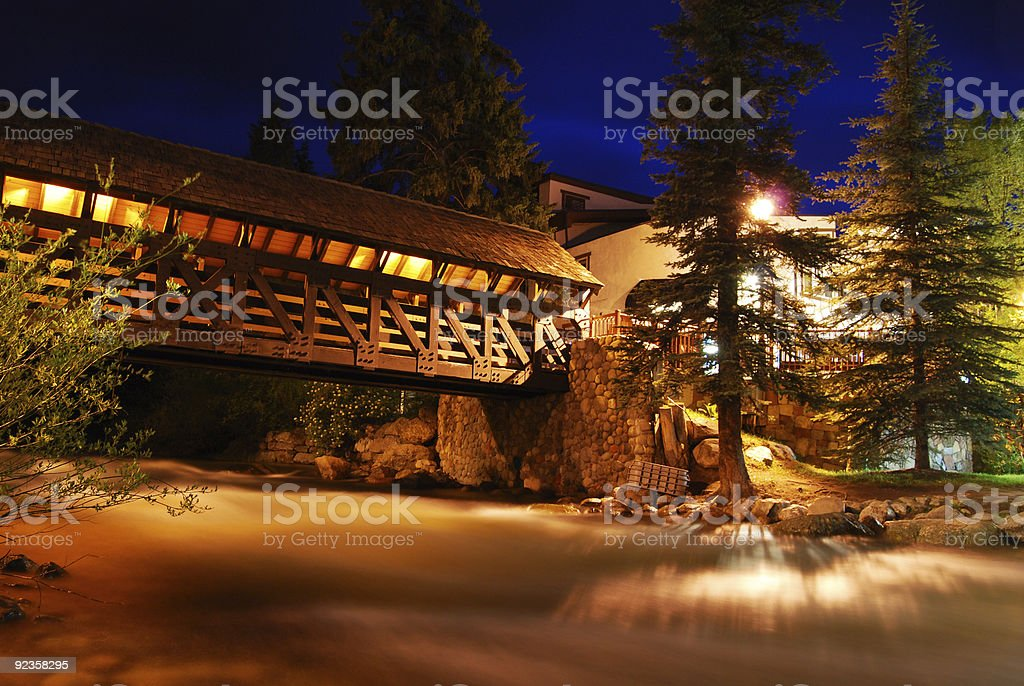 Foggy stream under covered bridge at night in Vail stock photo