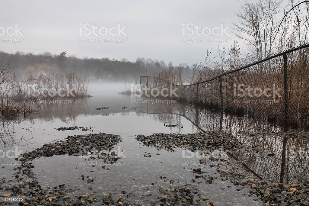 Foggy water scene with chain link fence stock photo