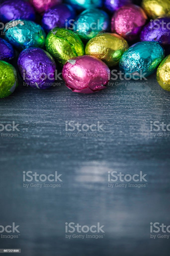 Foil covered Easter eggs on gray background stock photo