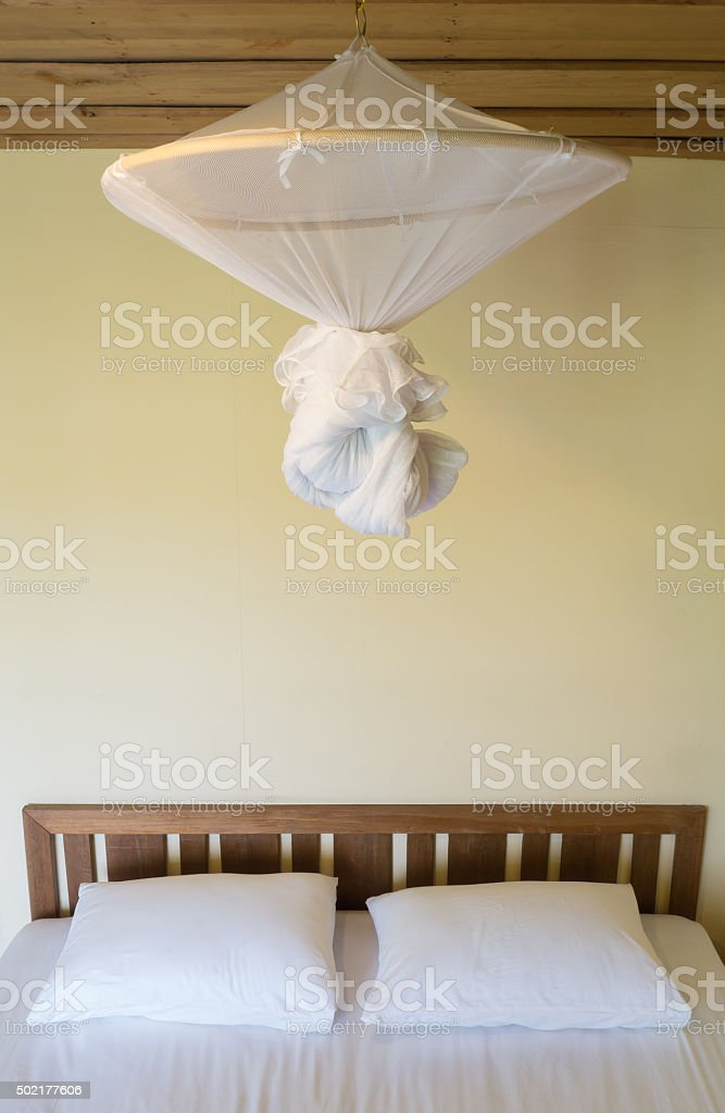 Fold mosquito net over a bed in bedroom. stock photo