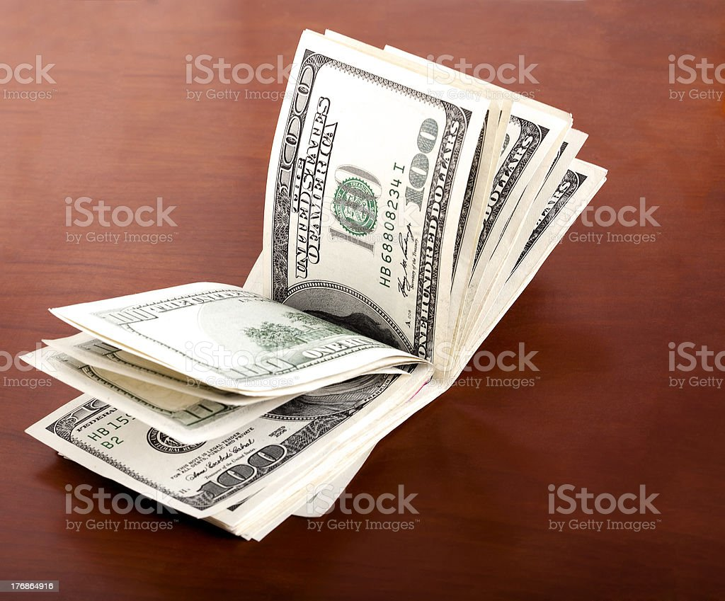 Folded 100 US$  Bills Stack on Brown Background royalty-free stock photo