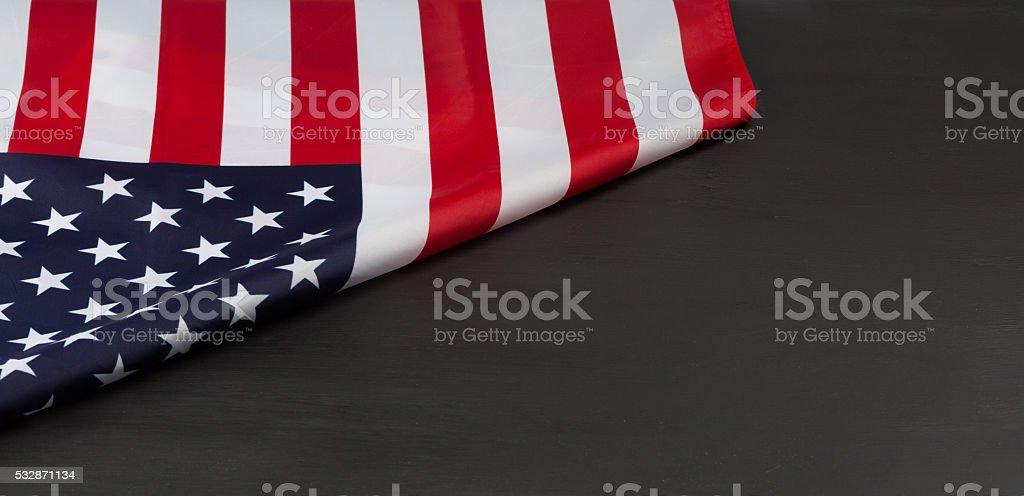 Folded american Flag on black chalkboard stock photo
