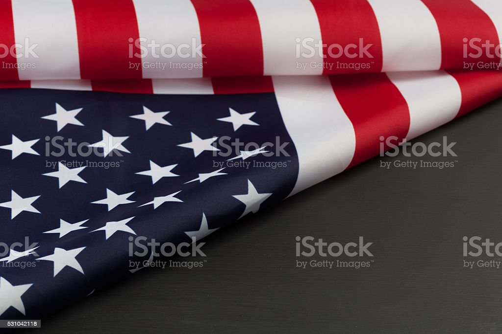 Folded american Flag on black chalkboard with copy space. stock photo