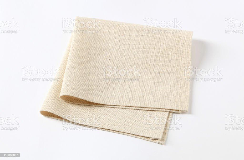 Folded beige textured napkin isolated on white background stock photo
