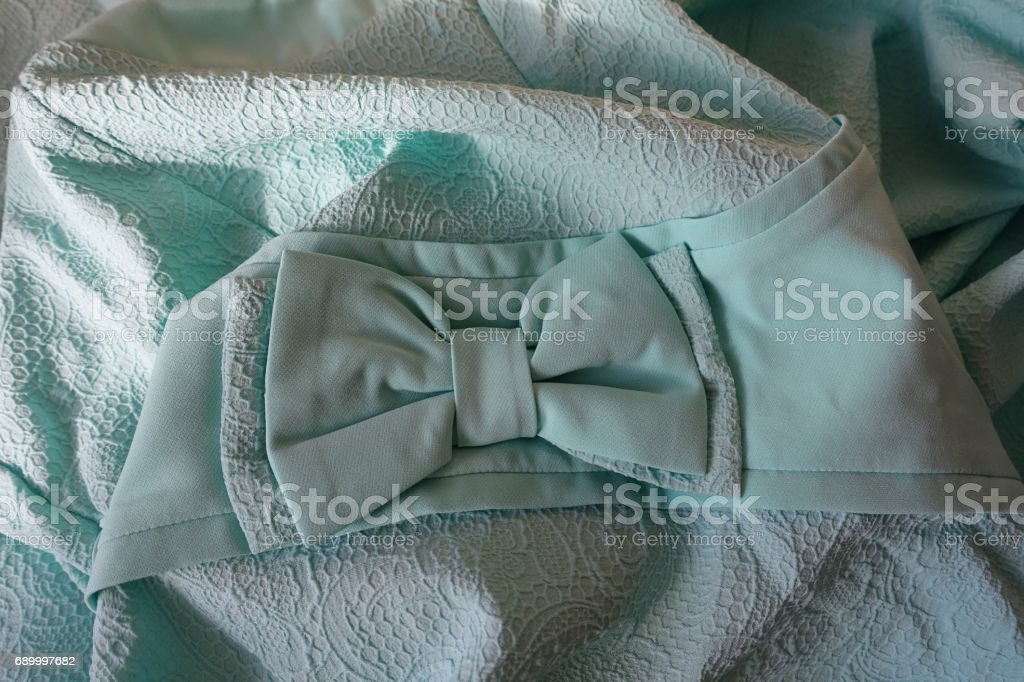 Folded bluish green fabric with bow and ribbon stock photo