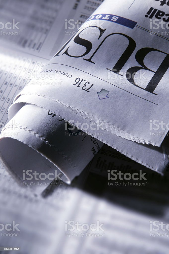 Folded business section of newspaper in early morning light royalty-free stock photo