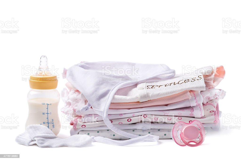 Folded clothes for babies with bottle of milk and pacifier stock photo