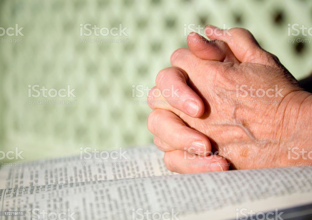 Folded Hands on Bible stock photo