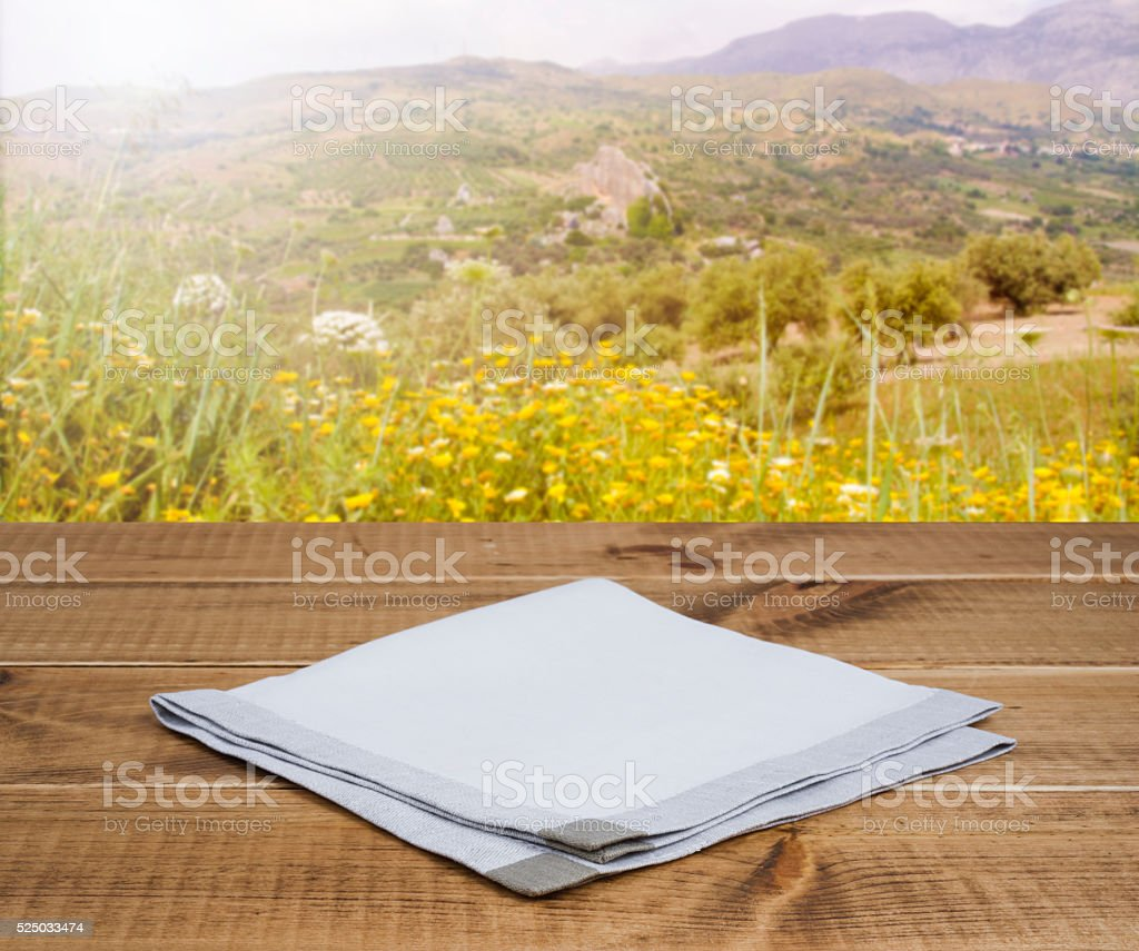 Folded linen napking on wooden table over mountain landscape background stock photo