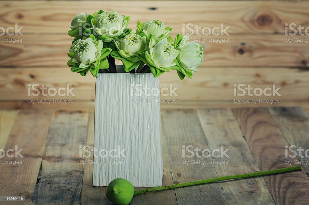 folded lotus flowers in vase on wooden background royalty-free stock photo