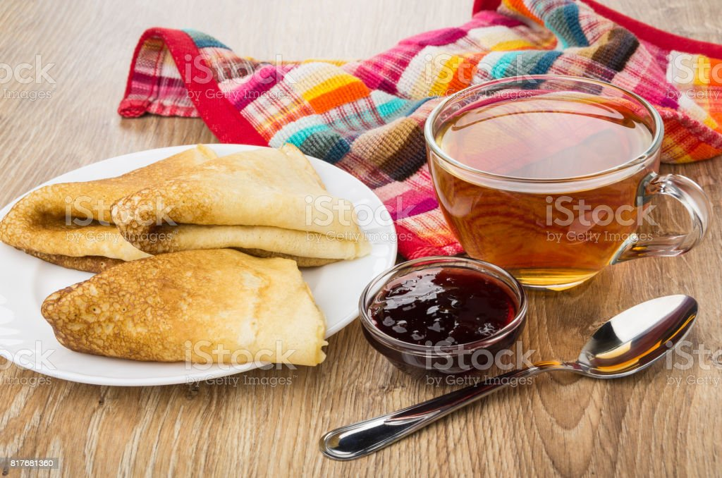 Folded pancakes in plate, cup of tea, cherry jam stock photo