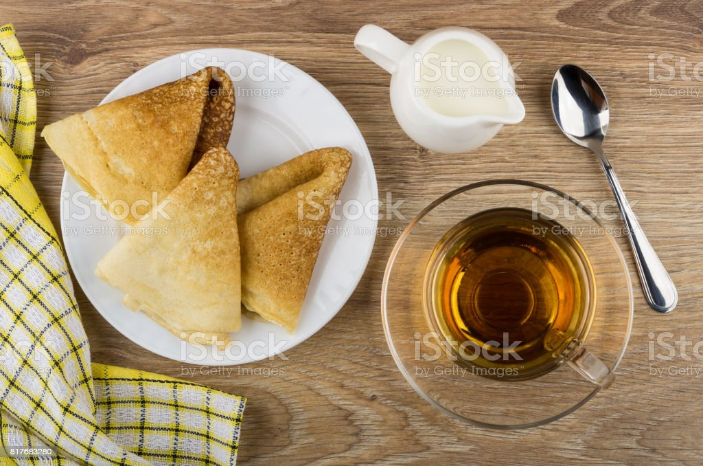 Folded pancakes in plate, cup of tea, jug of milk stock photo