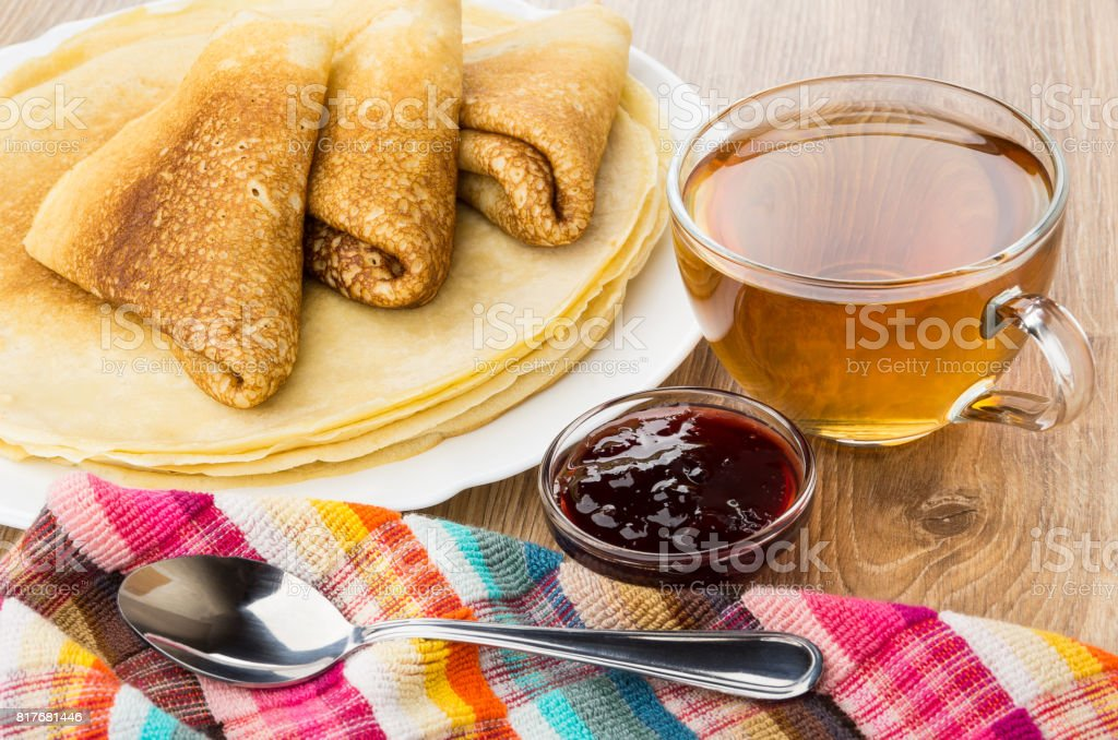 Folded pancakes on dish, tea, cherry jam in bowl stock photo