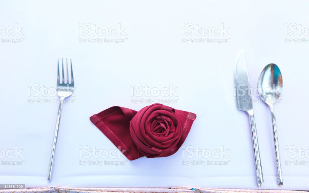 Folded Rose shape napkin with spoon, fork and knife stock photo