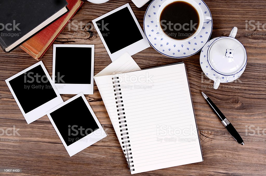 Folded spiral notebook with coffee and photo prints stock photo