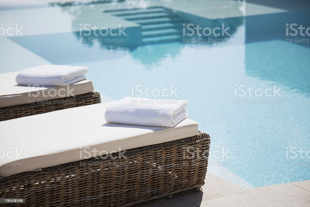 Folded towels on lounge chairs beside pool stock photo